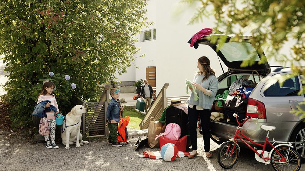 Famiglia in partenza per le vacanze si appresta a caricare l'auto
