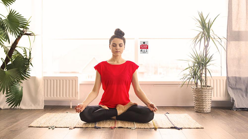 Donna medita in tranquillità grazie alla sicurezza offerta dall'allarme Verisure